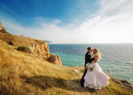 Just married - rocks, married, shore, grass, husband, bride, woman, clouds, sea, love, bright, just, sunrise, couple, ocean, wife, man, waves, sky, wedding, water, summer, passion, coast