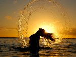 A view of the sunset and a lovey girl in water