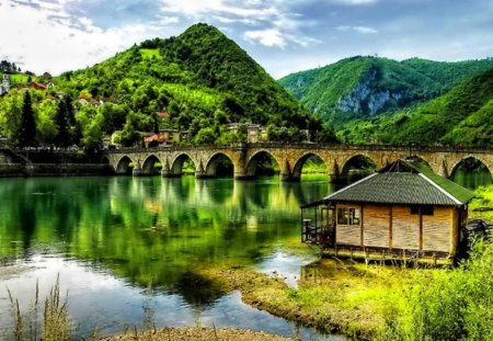 Bridge over the green river - lovely, greenery, clear, boat house, tranquility, pretty, green, beautiful, summer, lake, shore, riverbank, nature, bridge, peaceful, water, calm, calmness, house, nice, clouds, mirrored, river, mountain, cabin, cottage, emerald, serenity, sky, reflection