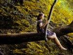 Bellissima ragazza seduta su un ramo d'albero