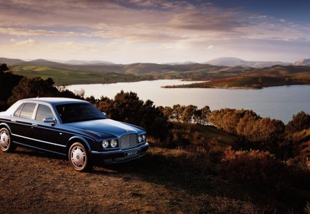 old bentley overlooking beautiful landscape - hill, trees, lake, car