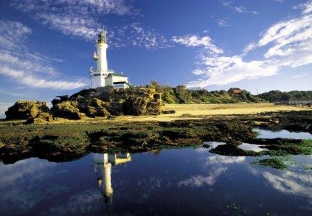 fantastic lighthouse reflected - hill, bridge, lighthouse, sea, rocks, shore