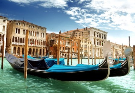parked gondolas in venice lagoon - lagoon, wooden stakes, boats, city