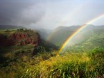 double rainbows in a green canyon