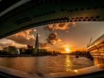 view of the thames river at sunset from under a bridge
