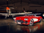 aircraft hanger and red car
