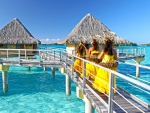 Intercontinental Thalasso Spa and Resort Bora Bora - Tahitian Girls walk on pontoon to water villas / bungalows