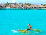 Polynesian Tahitian man blowing conch shell in canoe on perfect blue lagoon in Bora Bora French Polynesia