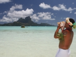 Tahitian Man blows conch shell to boat on blue lagoon on Bora Bora paradise tropical island Polynesia Tahiti