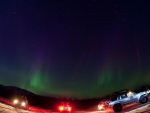 expedition trucks under northern light in fish eye