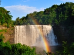 rainbow over cascading waterfalls