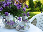 Garden table with flowers and tea