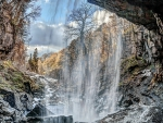 awesome waterfall over a rocky cavern hdr