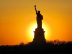 silhouette of the statue of liberty in sunset