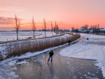 ice skating on a frozen river in holland