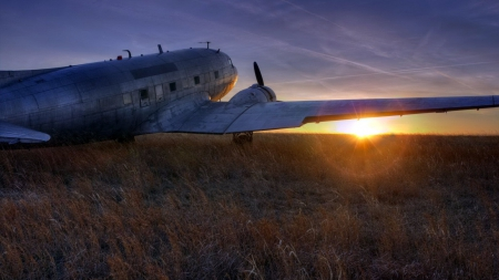 a DC-3 dakota on the prairie at sunset - plane, grass, prairie, sunset, prop