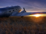a DC-3 dakota on the prairie at sunset