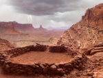 lightning over ancient ruins in a canyon