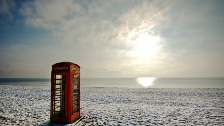 red phone booth on a beach - beach, sun, phone booth, reflected, sea