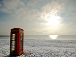 red phone booth on a beach