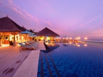 a seaside infinity pool in a resort at dusk