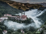 monastery on a hill in a foggy valley