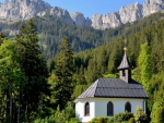 lovely chapel in forest under grand mountains