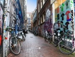bicycles in a graffiti painted alleyway in amsterdam