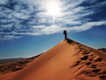 traveler atop a sand dune in a vast desert