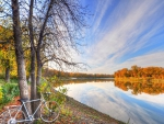 bicycle leaning on a tree by a rive hdr