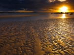 sunset on a rippled beach