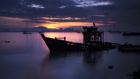 sunken boat in a malaysian harbor at twilight - sunken, city, boat, twilight, harbor