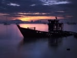 sunken boat in a malaysian harbor at twilight