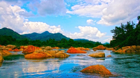 orange rocks in a flowing river - rocks, flowing, mountains, river, trees, clouds
