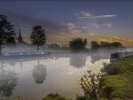 barges on a foggy thames river in lechlade england