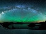 aurora borealis and the milky way above a lake