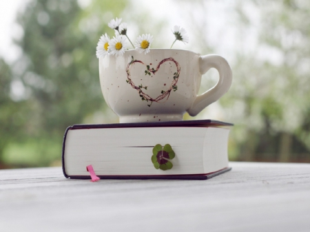 Book of Love - table, book, pink ribbon, trees, tea cup, still life, bokeh, heart, flowers