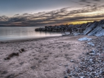 rocky wharf on a beach at twilight hdr