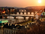 sunset over a river with many bridges in prague
