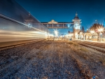 train passing a station at night in long exposure hdr