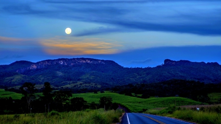 highway to mountains under moonlight - grass, blacktop, highway, moon, mountains, trees