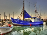blue commercial sailboat docked hdr