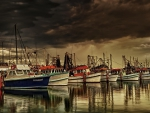 fishing boats in a marina under stormy skies hdr