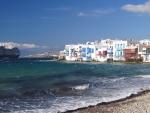 cruise ship sailing by a mykonos beach