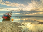boat aground on a beach at low tide hdr