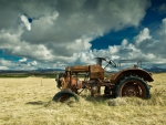 old rusty tractor in hay field