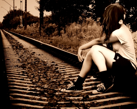 on the edge of a railway track - grass, trains, pebbles, edge, track, metal, railway, stones, train, green, person, flowers, holiday, girl, converse, sitting, nature, white, field