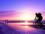 biking on a beach in a purple sunset