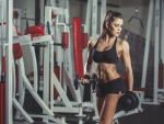 Sexy girl with dumbbells in the gym