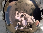 Astronaut Stephen Robinson repairs damage to Space Shuttle